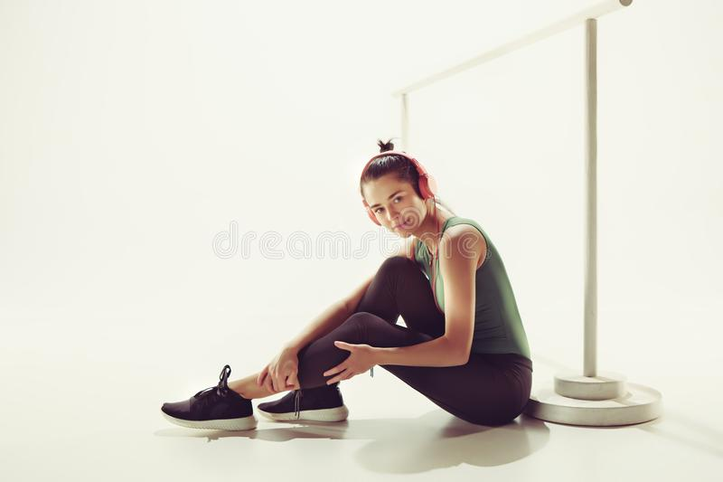 Opinião dianteira uma jovem mulher que senta-se com fones de ouvido imagens de stock