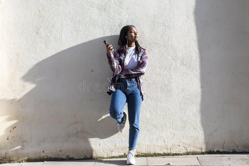 Opinião dianteira uma mulher afro-americano de sorriso nova que está fora ao sorrir e música de escuta por fones de ouvido em um  fotografia de stock