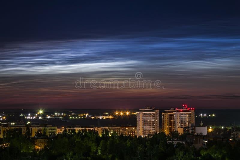 Opinião do céu noturno de nuvens noctilucent bonitas sobre a cidade com uma arquitetura da cidade no primeiro plano imagens de stock royalty free