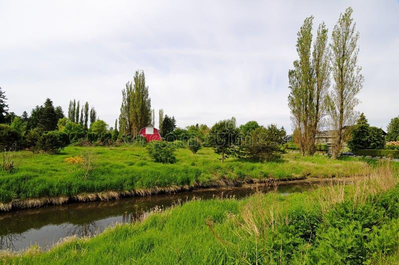 Opinião do campo com prado verde e o celeiro vermelho imagem de stock