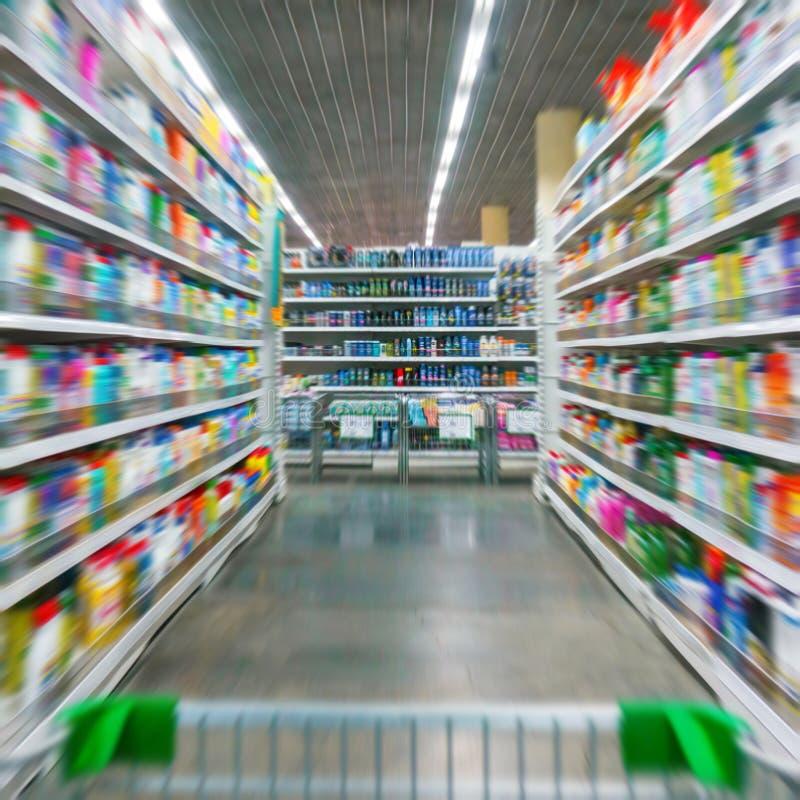 Opinião do carrinho de compras em um corredor e em prateleiras do supermercado - a imagem tem a profundidade de campo rasa fotografia de stock royalty free