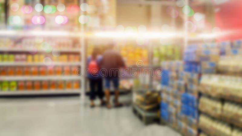 A opinião do carrinho de compras no corredor do supermercado com sumário das prateleiras do produto borrou imagens de stock royalty free
