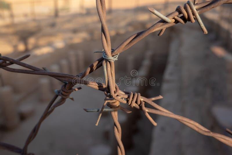 Opinião do close-up do arame farpado oxidado de uma cerca para um campo da escavação em Sudão fotografia de stock