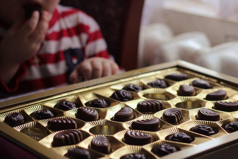 Opinião do close up da caixa dos chocolates Criança que come doces greed foto de stock royalty free