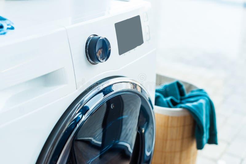 opinião do close-up da máquina de lavar e da cesta modernas com lavanderia em casa foto de stock royalty free