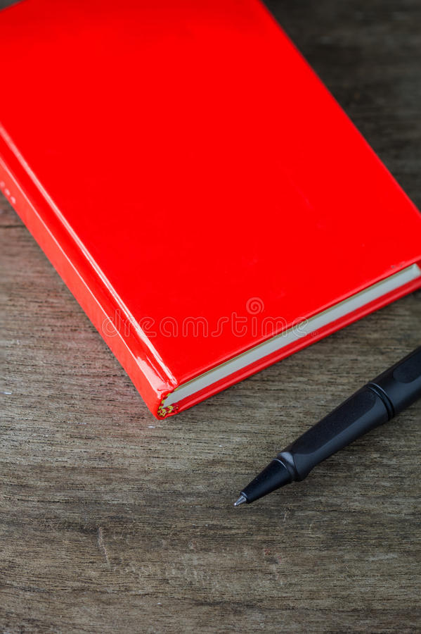 Opinião do close-up da pena e do caderno vermelho imagem de stock royalty free