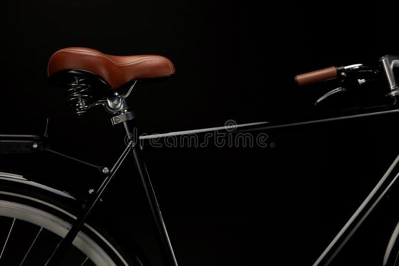 opinião do close-up da sela e do guiador da bicicleta clássica isolados no preto fotos de stock