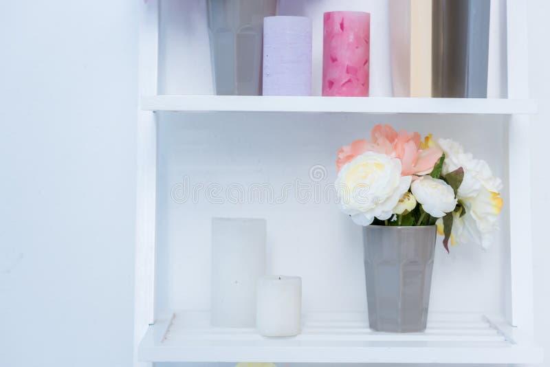 opinião do close-up das prateleiras de madeira brancas com livros, velas e flores fotos de stock