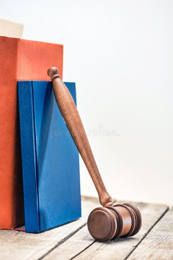 Opinião do close-up do malho de madeira do juiz e dos livros na tabela de madeira foto de stock