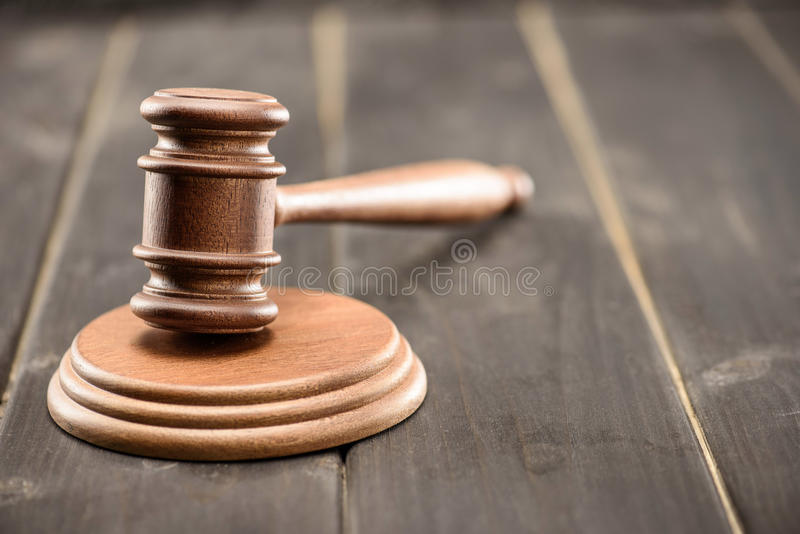 Opinião do close-up do malho marrom do juiz na tabela de madeira foto de stock