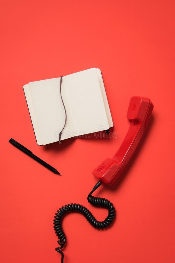 Opinião do close-up do monofone de telefone do vintage e do caderno aberto da placa com pena imagem de stock royalty free