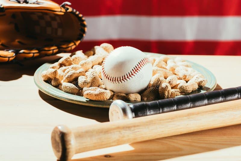opinião do close-up dos bastões de beisebol, da bola do basebol na placa com amendoins e da luva de couro na tabela de madeira co imagem de stock royalty free