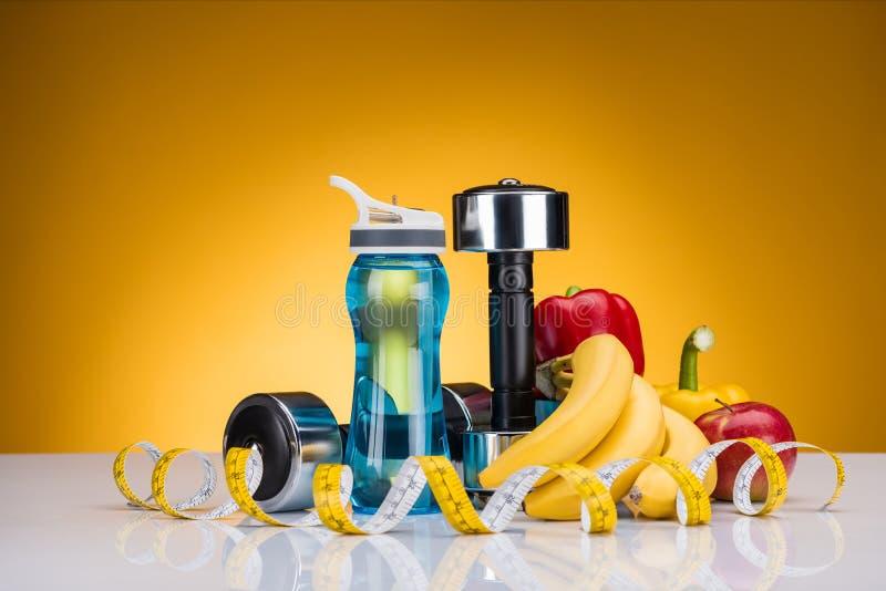 opinião do close-up dos pesos, da garrafa da água, da fita de medição e das pimentas com frutos fotografia de stock