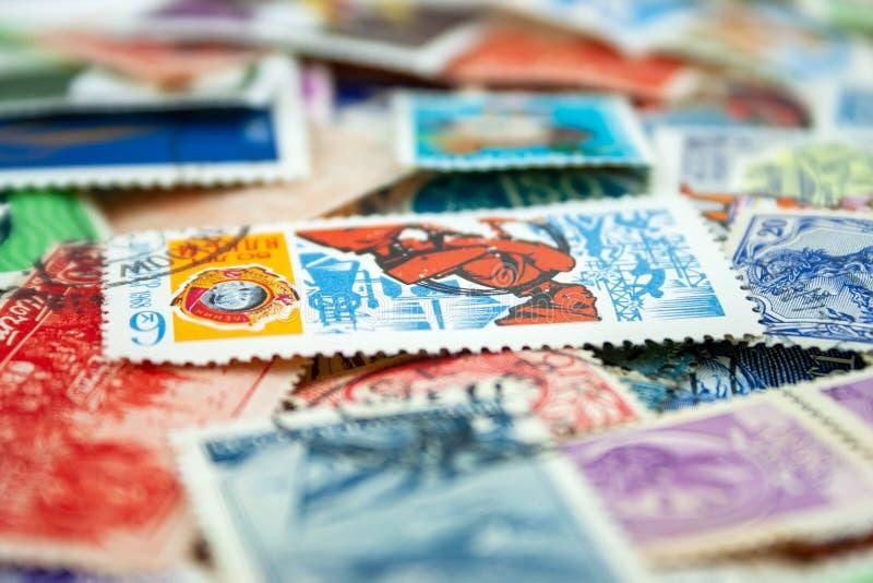 Opini?o do close up em uma variedade de selos postais multi-coloridos dos pa?ses diferentes e dos anos Foco seletivo fotos de stock
