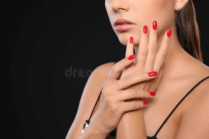 Opinião do close up a jovem mulher bonita com tratamento de mãos brilhante no fundo preto Tend?ncias do verniz para as unhas fotografia de stock