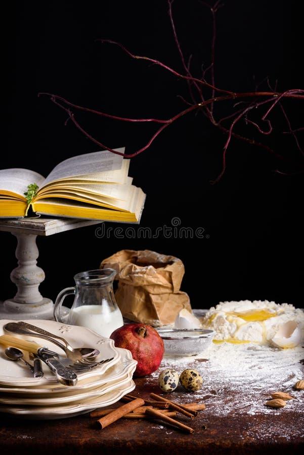 Opinião do close-up do livro e de ingredientes abertos para fazer a massa no tampo da mesa imagens de stock royalty free