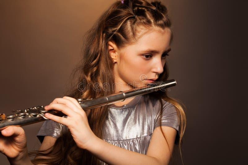 Opinião do close-up a menina que joga na flauta de prata foto de stock