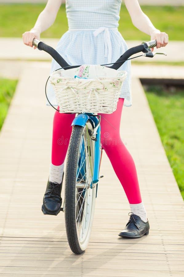 Opinião do close-up a mulher que está em uma bicicleta azul do vintage imagens de stock
