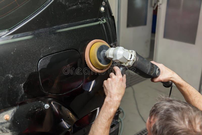 Opinião do close-up nas mãos de um trabalhador masculino que guarde uma ferramenta para lustrar o para-choque de um carro ao trab foto de stock royalty free