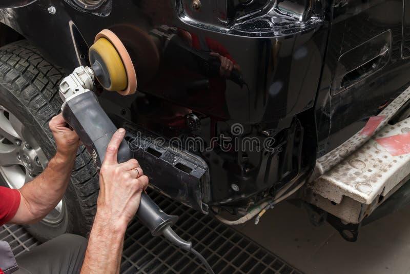 Opinião do close-up nas mãos de um trabalhador masculino que guarde uma ferramenta para lustrar o para-choque de um carro ao trab imagens de stock