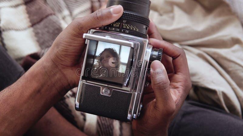 Opinião do close-up o homem africano que guarda o photocamera velho, tomando a retrato da foto a mulher bonita Pares multirraciai fotos de stock royalty free