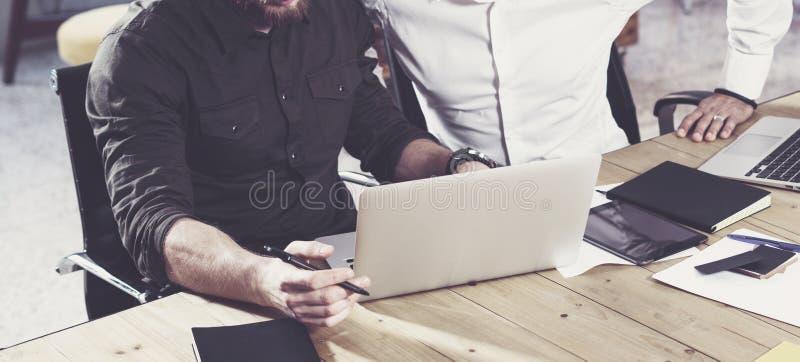 Opinião do close up o homem farpado que trabalha junto com o colega no projeto startup novo Executivos do conceito dos trabalhos  fotos de stock royalty free