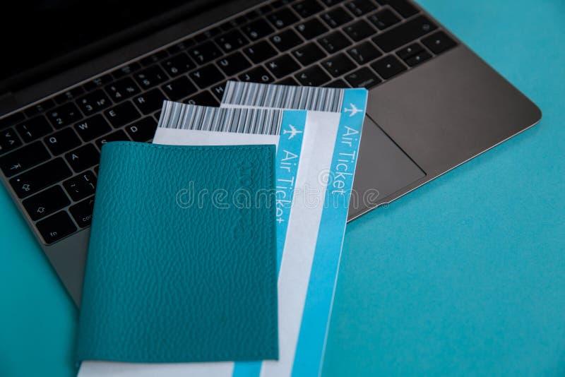 Opinião do close up do passaporte e de bilhetes azuis para dentro no portátil imagem de stock