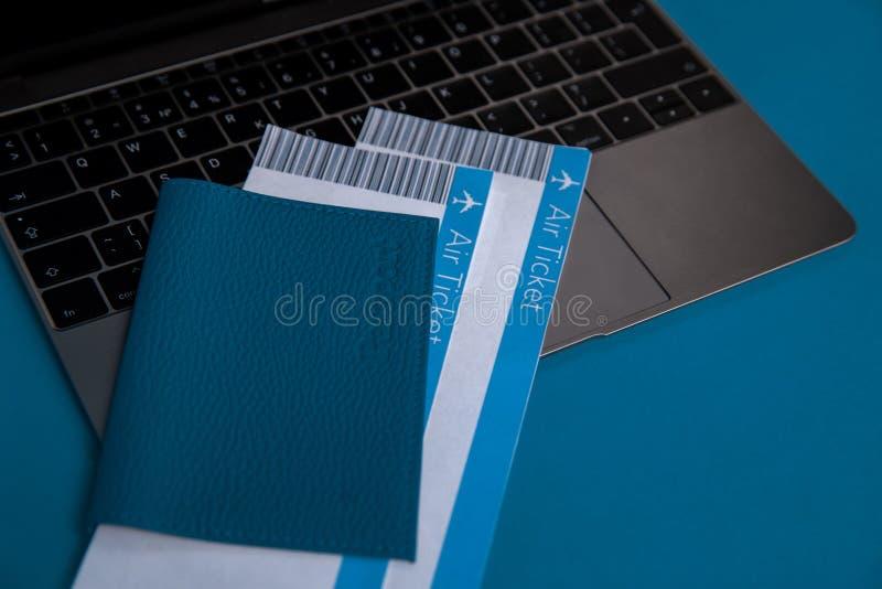 Opinião do close up do passaporte e de bilhetes azuis para dentro no portátil fotos de stock