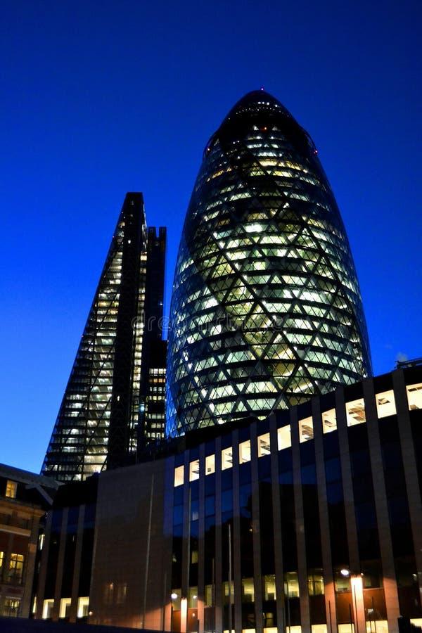 Opinião do close-up a uma arquitetura do pepino do pepino e arranha-céus de Cheesegrater na noite fotos de stock royalty free