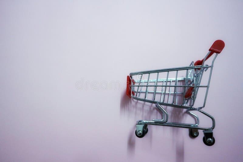 Opinião do close-up, vista superior, carrinho de compras vermelho no fundo cor-de-rosa fotografia de stock royalty free