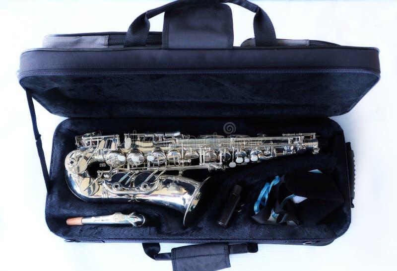Opinião do close-up, vista superior, instrumento do saxofone na caixa negra, único objeto isolado, fundo branco fotografia de stock