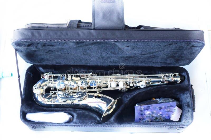 Opinião do close-up, vista superior, instrumento do saxofone na caixa negra, único objeto isolado, fundo branco foto de stock