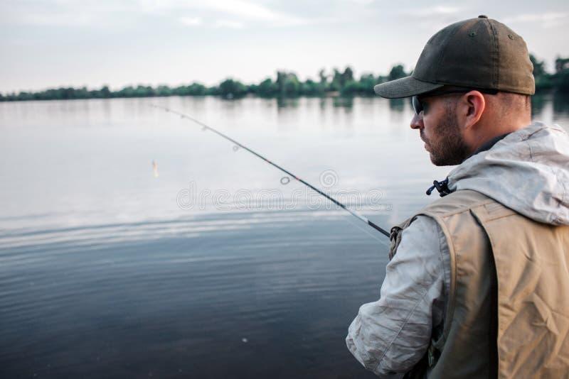 A opinião do corte o pescador está com sua parte traseira na câmera Está olhando à direita O indivíduo tem a haste de mosca nas m fotografia de stock