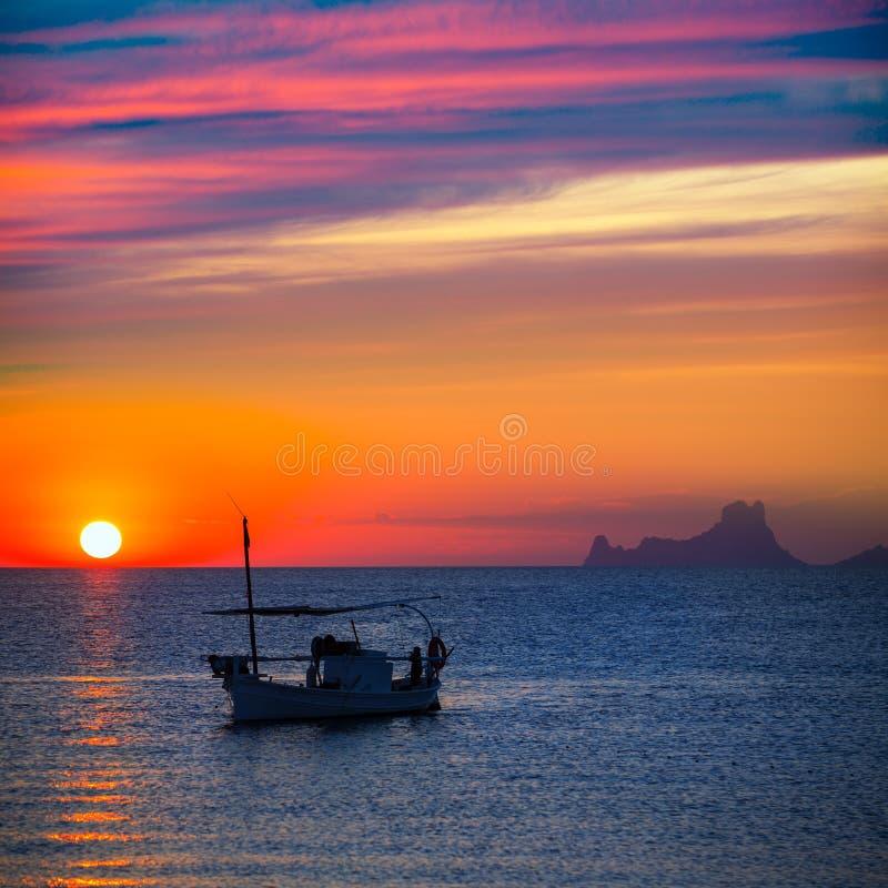 Opinião do Es Vedra do por do sol de Ibiza e barco de pesca formentera fotografia de stock
