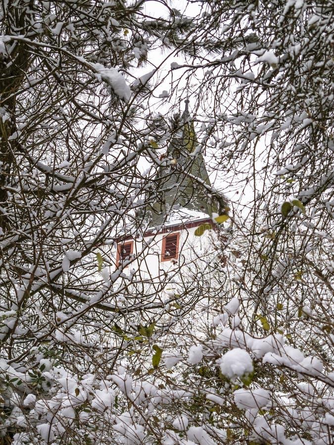 Opinião do inverno de uma torre de igreja coberta completamente com os ramos da neve em Kronenburg, Reno-Westphalia norte, Aleman imagem de stock royalty free