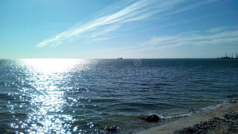 Opinião do mar da costa em um dia ensolarado Mar calmo com ondinhas claras na superfície da água, brilho do sol, céu azul com cl  imagem de stock royalty free