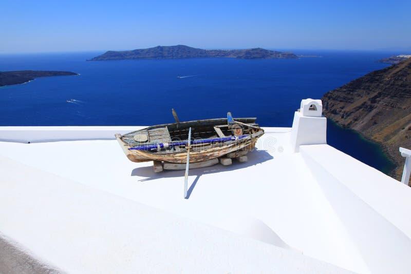 Opinião do mar e um barco velho em um telhado em Santorini fotografia de stock
