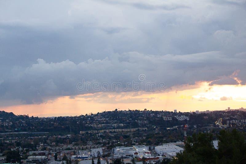 Opinião do montanhês das casas e das ruas com o céu panorâmico que mostra em silhueta skyscrappers do centro imagem de stock royalty free