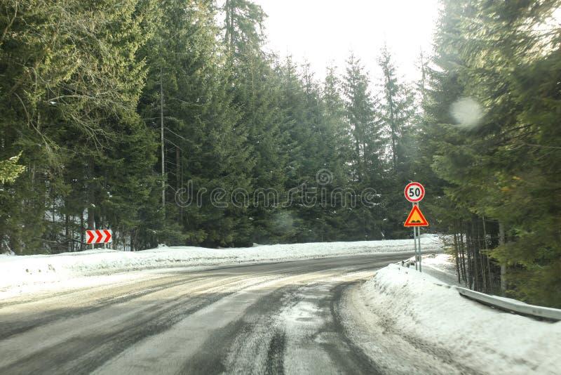 Opinião do motorista na curva afiada da estrada, coberta parcialmente com a neve dentro imagens de stock