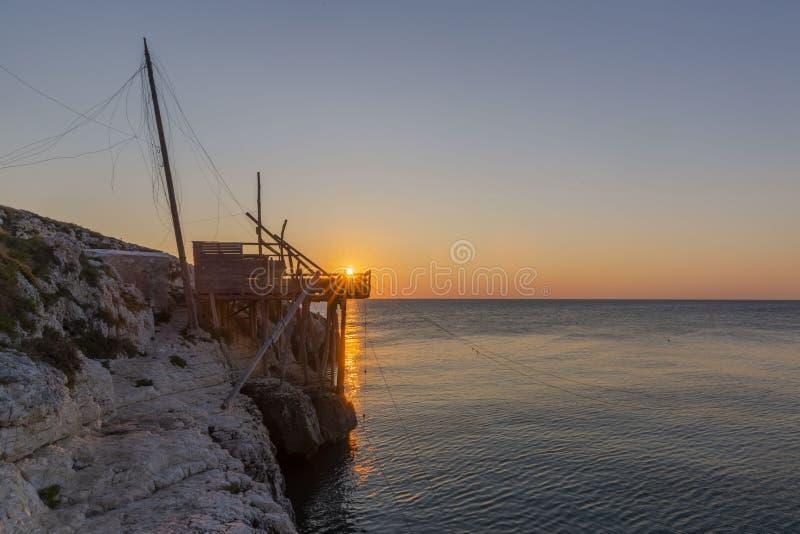 Opini?o do nascer do sol de Trabucco que pesca a casa em Vieste, It?lia fotos de stock