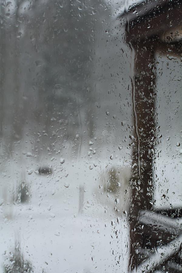 Opinião do pátio através de uma janela de vidro molhada fotografia de stock royalty free