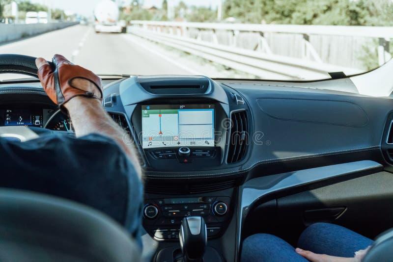 Opinião do painel e mapa de GPS do carro moderno com mãos do motorista On Steering Wheel imagem de stock royalty free