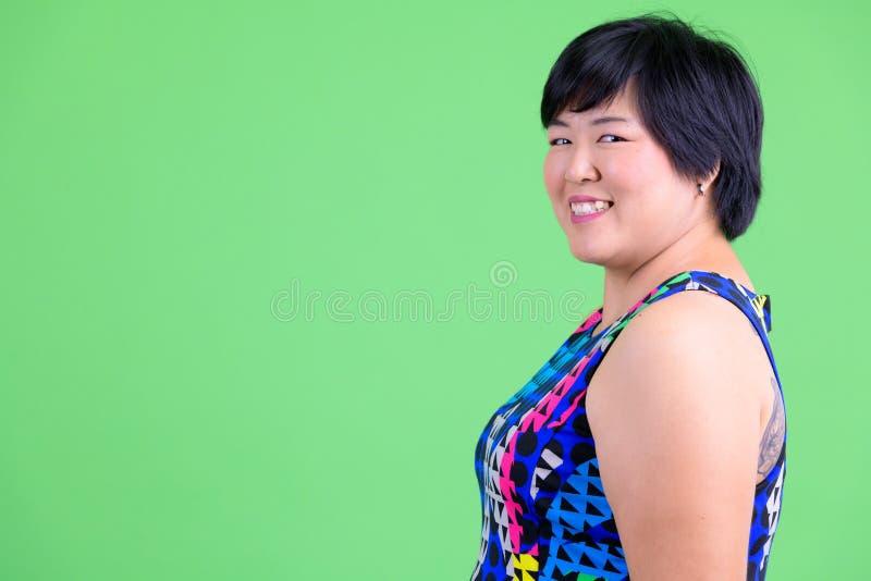 Opinião do perfil do close up a mulher asiática excesso de peso feliz nova que olha pronta para a reprodução fotográfica ao parti fotos de stock royalty free