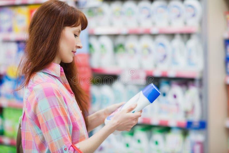 Opinião do perfil a mulher que escolhe o detergente foto de stock royalty free
