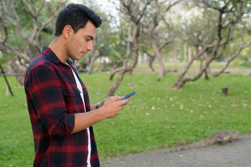 Opinião do perfil o homem latino-americano considerável novo do moderno que usa o telefone no parque fotos de stock
