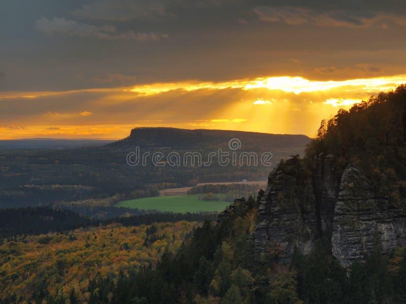 A opinião do por do sol do outono sobre o arenito balança ao vale colorido da queda de Suíça boêmio Picos do arenito na floresta imagem de stock