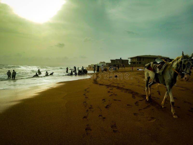 A opinião do por do sol dos falcões late praia karachi foto de stock