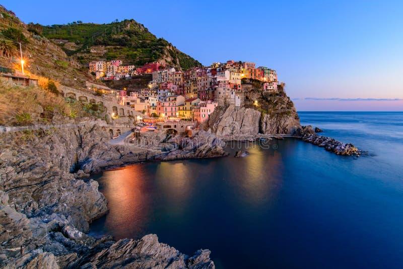 Opinião do por do sol e da noite Manarola, uma das cinco vilas mediterrâneas em Cinque Terre, Itália, famoso para suas casas colo imagens de stock