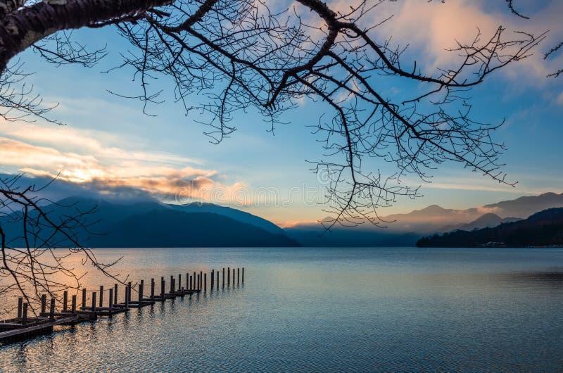 opinião do por do sol do lago Chuzenji com cais, árvore e montanhas perto de Nikko, Japão, fundo do outono fotos de stock royalty free