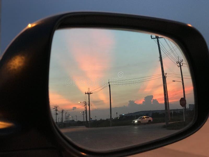 Opinião do por do sol para trás no espelho de carro fotografia de stock
